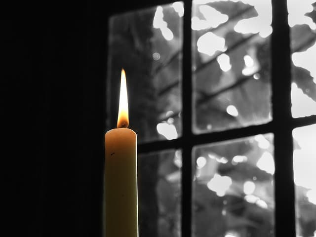 A candle in front of a wintery window.